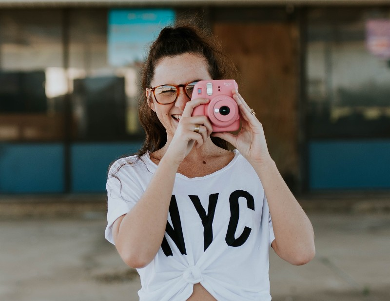 Picture of a girl taking a photo with an Instax Mini 9 Camera