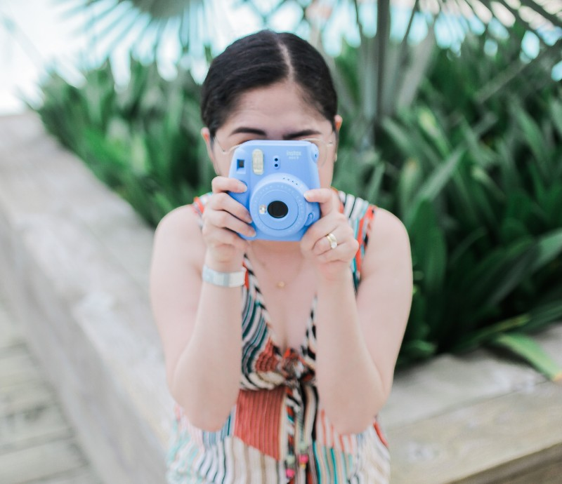 Picture of another woman taking a photo with an Instax Mini 9 camera.